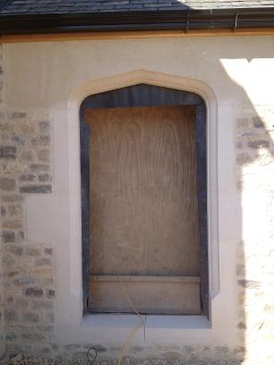 Bath stone arched doorway set in Purbeck stone walling .