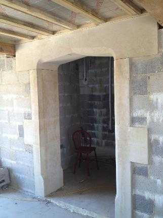 Internal arched stone doorway in Bath stone .
